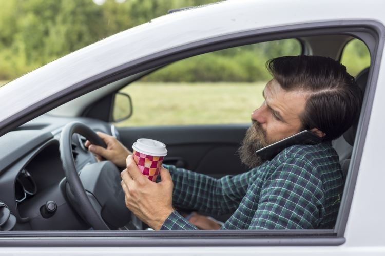 Man driving while distracted with phone and coffee